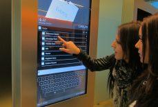 Zwei Schülerinnen bedienen auf einer A-Design Stele die Personensuche über die A-Design Organizer - Software